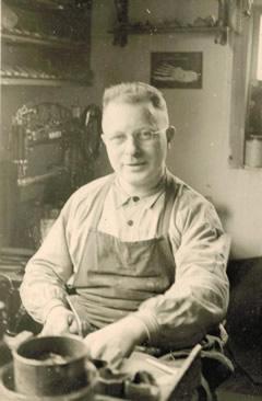 Gottfried Oberle mit Adlernähmaschine im Hintergrund